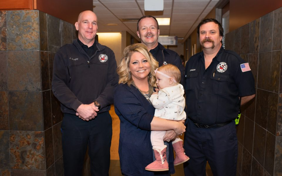 Blonde woman holding infant standing in front of three paramedics