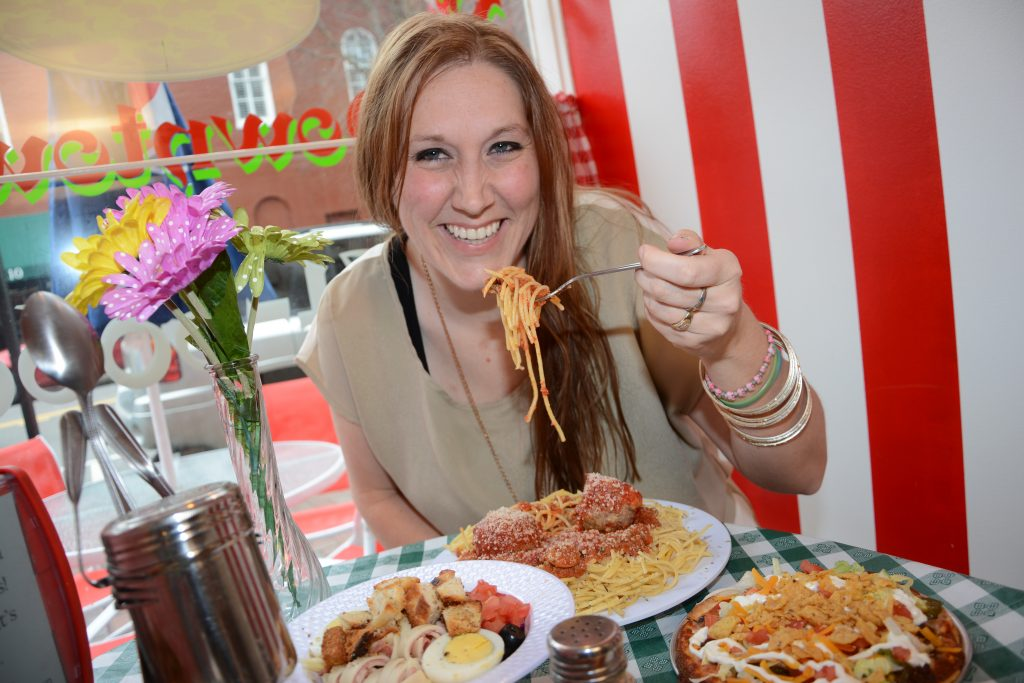 Young woman in restaurant eating pasta