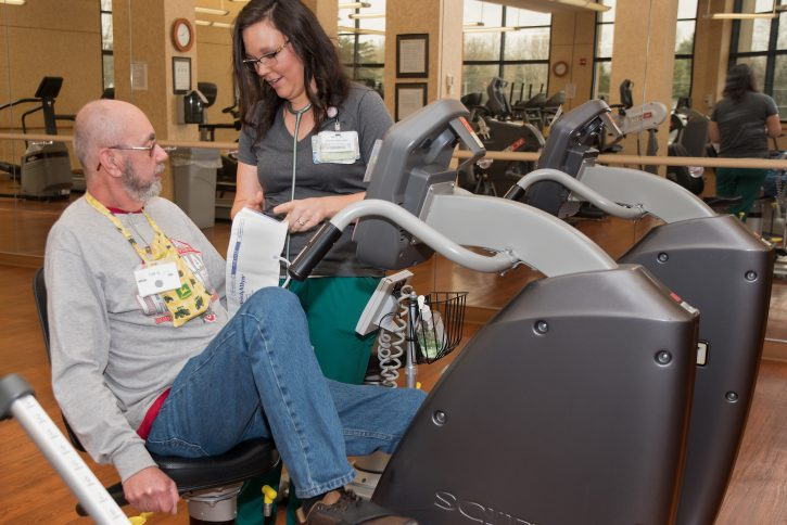 Man in grey sweatshirt on stationary bike next to nurse