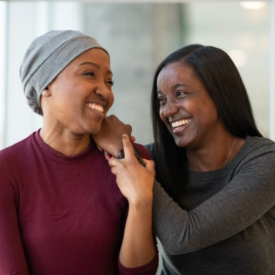 Young African American woman with cancer spends time with a friend.