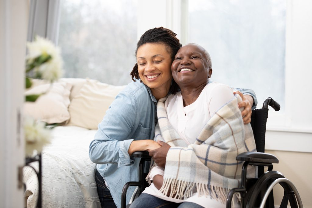 Young woman hugs senior woman in wheelchair
