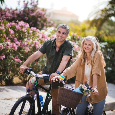 Smiling active senior man and woman riding bicycles in spring