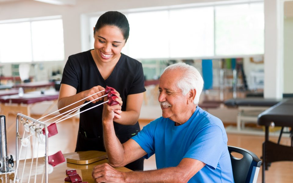 Happy senior man exercising hand with physical therapy device