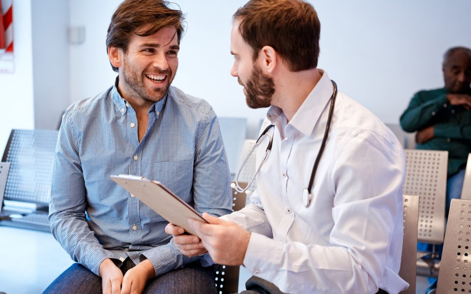 Smiling man looking at doctor with clipboard