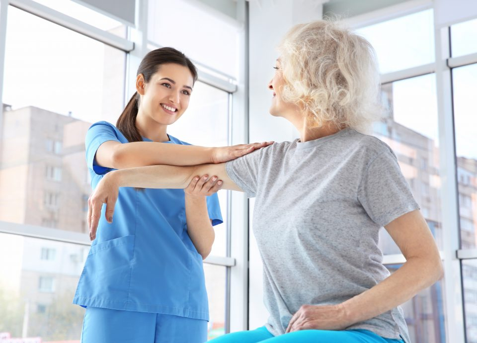 Female provider helps senior woman to stretch her arm