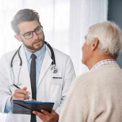 young male doctor going through medical records with his senior male patient