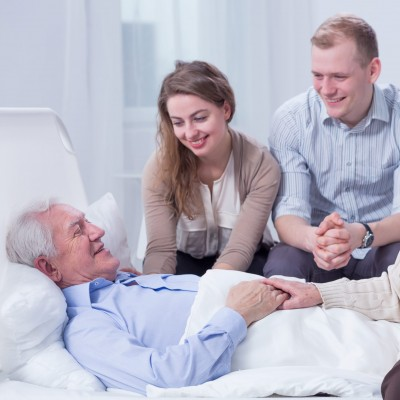 Old man lying in a white hospital bed, surrounded by his smiling relatives