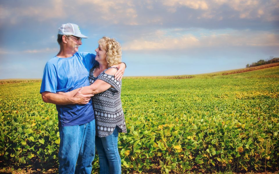Lung cancer survivor embracing partner in a field