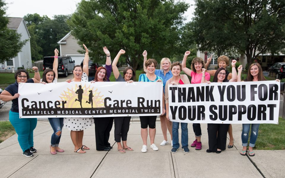 Fundraising group holding up sign to thank participants of a run