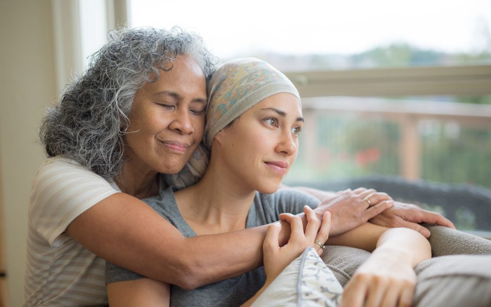 Young woman in cancer treatment being embraced by her mother.
