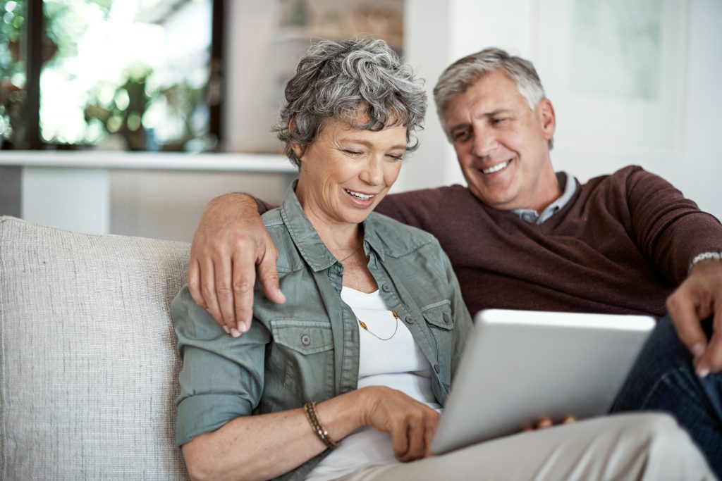 mature couple using a digital tablet while relaxing on their sofa