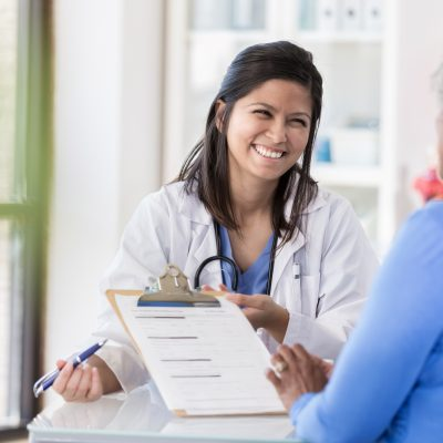 Female doctor laughs with patient during paperwork
