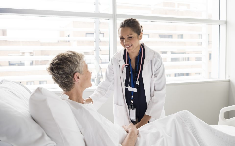 Female healthcare provider talking with female patient in a hospital bed