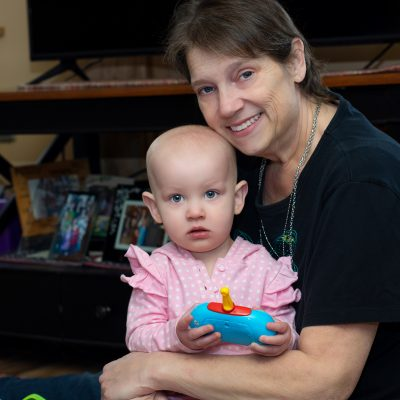 Woman sits on ground with one year old granddaughter