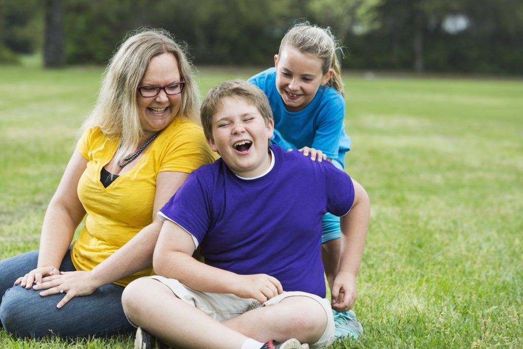 Mother and two children laughing in the park