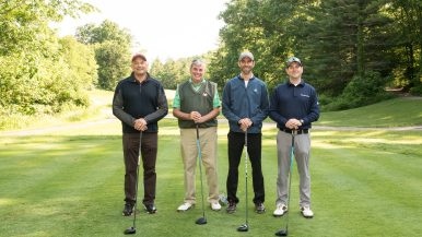 Four men posing on the golfing greens at Westchester Golf Course with their golf clubs