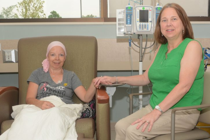 Paula Tipple holds hands with FMC volunteer during cancer treatment