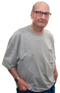 Elderly gentleman stands against white background in grey shirt