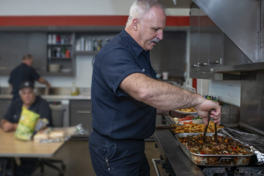 Man in uniform serving himself food in kitchen