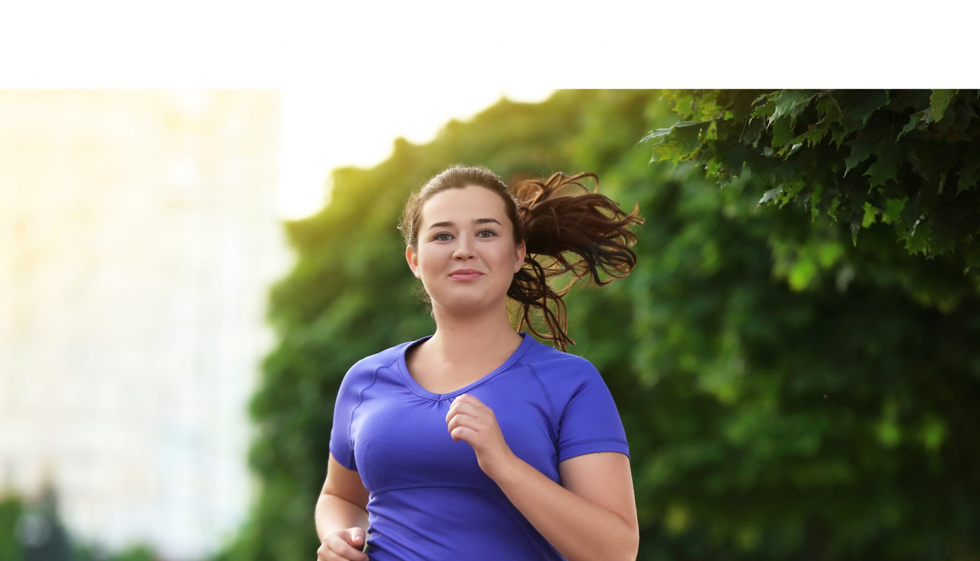 Young woman with dark hair running, tree in background