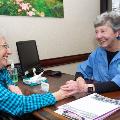 Volunteer smiling at female cancer patient at a desk