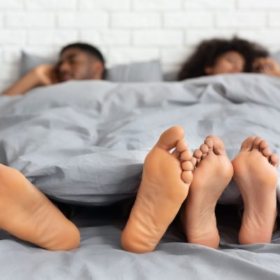 Couple sleeping with feet out