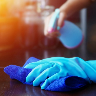 Person cleaning with rubber gloves on and towel