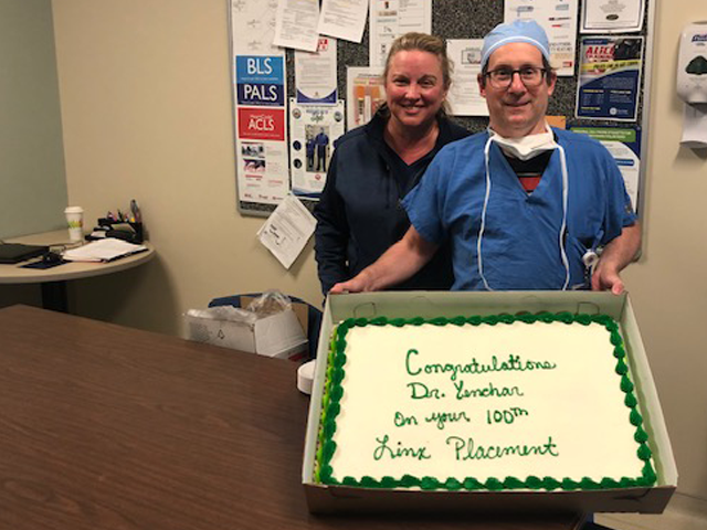 Dr. Yenchar and Tonya Mundy hold a celebratory cake
