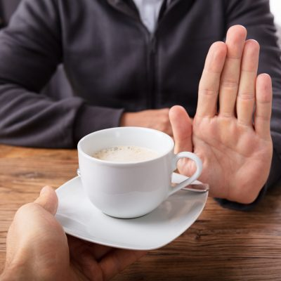 Person refusing cup of coffee