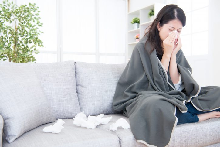 Woman Blows nose on Couch